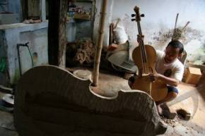 An Indonesian luthier working on a Keroncong Cello. Note there are only three pegs.