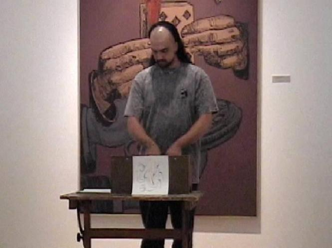 "Jon Silpayamanant performing a score by Dick Higgins on a toy piano at ""Betwixt and Between: The Life and Work of Fluxus Artist Dick Higgins"" At the Peeler Art Gallery September 5, 2002"